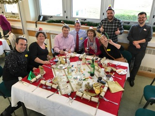 The Blind Veterans IT team wearing Christmas party hats and sat around a Christmas meal