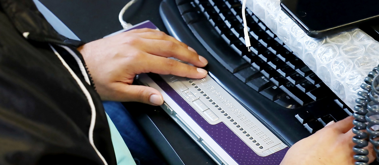 Close up of hands using braille display with keyboard and mobile phone in the background