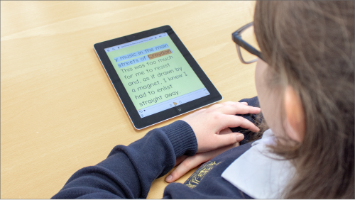Young student in uniform looking at their tablet running EasyReader.