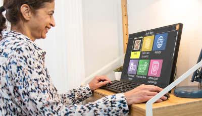 Cheerful lady using GuideConnect on a desktop computer.