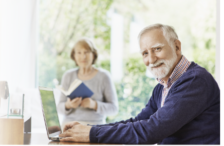Man using laptop at home with lady in the background reading a book