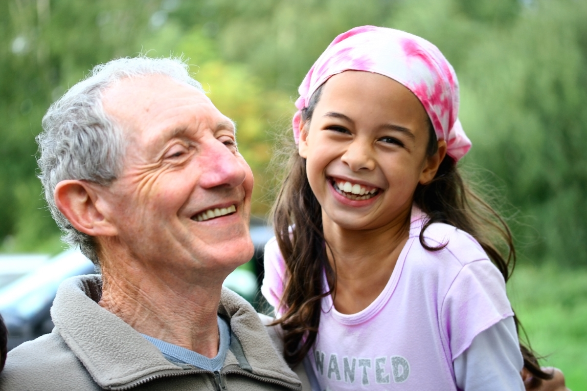 Older man and young girl outdoors laughing