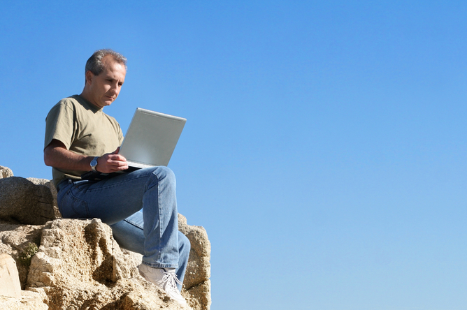 Man sitting on rocks looking at a laptop with blue skies behind him