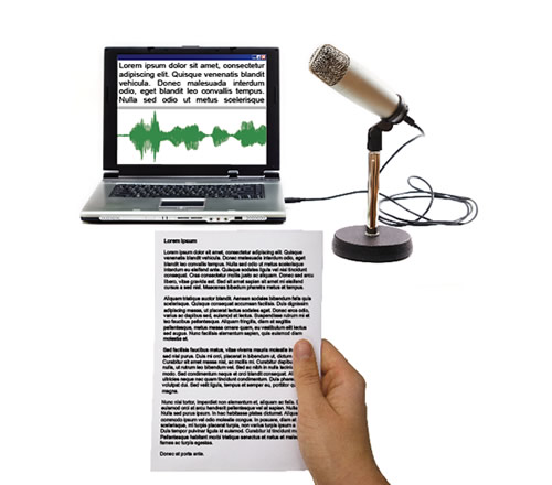 A laptop with Publisher on the screen, a microphone and a hand holding piece of paper with text on.