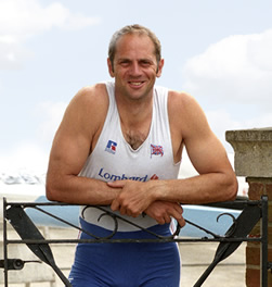 Photo of Sir Steve Redgrave dressed in his British Championship Rowing outfit, smiling and leaning on a gate