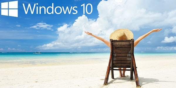 Windows 10 logo in the blue sky. Lady sat on a deckchair on the beach, arms overhead.