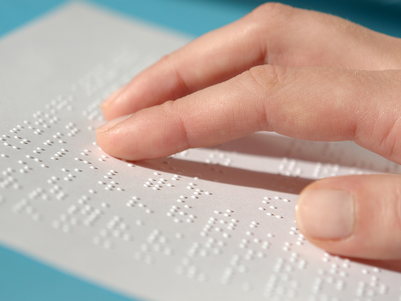 Image of a hand touching a sheet of embossed Braille